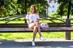 De mooie donkerbruine meisjeszitting op een bank in de zomer zonnig park, lezings sociaal netwerk, geniet van uw vakantie, studen Stock Afbeeldingen