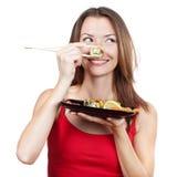 De mooie donkerbruine sushi van de vrouwenholding Stock Afbeeldingen
