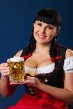 De mooie donkerbruine vrouw in Beiers kleedde zich met glas bier Stock Afbeeldingen