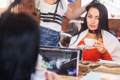 De mooie donkerbruine vrouw bij de kapperstilist zit dichtbij de spiegel en drinkt koffie Royalty-vrije Stock Foto
