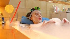 De mooie donkerbruine vrouw die kosmetisch gezichtsmasker dragen ontspant in schuimend bad Schoonheidsbehandeling thuis 4k schot stock footage
