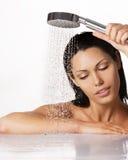 De mooie donkerbruine vrouw houdt douche in handen Royalty-vrije Stock Foto's