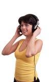 De mooie donkerbruine vrouw is luistert aan de muziek bij hoofdtelefoons Stock Afbeeldingen