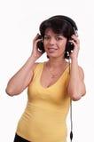 De mooie donkerbruine vrouw is luistert aan de muziek bij hoofdtelefoons Royalty-vrije Stock Afbeeldingen