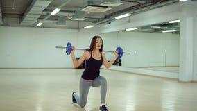 De mooie donkerbruine vrouw maakt uitvalt met een barbell in de gymnastiek royalty-vrije stock foto's