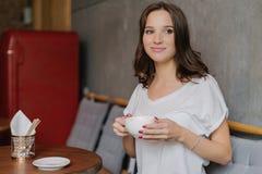 De mooie donkerbruine vrouw met dromerige uitdrukking, heeft koffiepauze na het werk, draagt witte t-shirt, doorbrengt vrije tijd stock foto