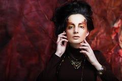 De mooie donkerbruine vrouw met heldere creatief maakt omhoog Royalty-vrije Stock Afbeeldingen