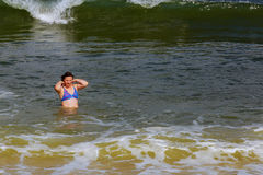 de mooie donkerbruine vrouw stelt blauwe oceaan in werking Stock Foto's