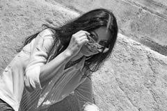 De mooie donkerbruine vrouw vermindert haar zonnebril om een blik te nemen Royalty-vrije Stock Foto's
