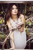 De mooie donkerbruine vrouw in witte kleding en sensueel stelt in cactustuin Royalty-vrije Stock Foto's
