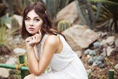 De mooie donkerbruine vrouw in witte kleding en sensueel stelt in cactustuin Royalty-vrije Stock Afbeeldingen