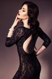 De mooie donkerbruine vrouw in zwarte kleding met avond maakt omhoog en Stock Afbeelding