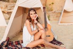 De mooie donkerbruine zitting van het hippiemeisje bij de tent Royalty-vrije Stock Afbeeldingen