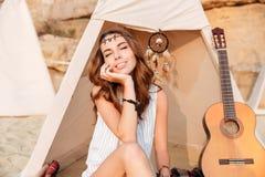 De mooie donkerbruine zitting van het hippiemeisje bij tent met gesloten ogen Stock Foto