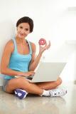 De mooie doughnut van de vrouwenholding terwijl het surfen van het Web royalty-vrije stock afbeelding
