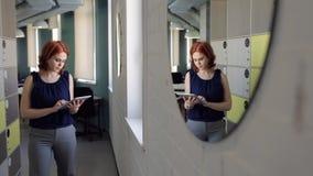 De mooie drukken van de gembervrouw op tablet op kantoor stock videobeelden