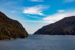 De mooie Duistere Geluiden in Fjordland, Nieuw Zeeland, met een blauwe hemel en aardige wolken stock fotografie