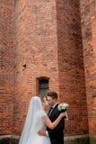De mooie echtgenoot van het huwelijkspaar in kostuum en de vrouw in huwelijk kleden het stellen dichtbij de muur stock foto