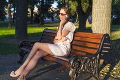 De mooie emotionele donkerbruine meisje het lachen de zomerglazen van het telefoonpark roze kleding, genieten van uw vakantie in  Stock Afbeelding