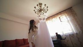 De mooie en mooie bruid in nachttoga houdt hanger met een huwelijkskleding De kat zit dichtbij vrouw Huwelijksochtend stock videobeelden