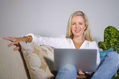 De mooie en gelukkige elegante blonde vrouw vroege jaren '40 ontspande thuis woonkamer gebruikend Internet op laptop computer die stock foto
