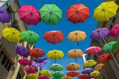 De mooie en kleurrijke paraplu's hingen het midden van de gebouwen Royalty-vrije Stock Fotografie