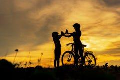 De mooie familie van de silhouetfietser bij zonsondergang over de oceaan Mamma en dochter ontspant de bicycling kou en bij het st royalty-vrije stock fotografie