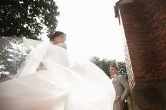 De mooie gang van het jonggehuwdepaar dichtbij oude christelijke kerk royalty-vrije stock foto's
