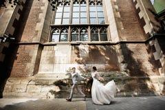 De mooie gang van het jonggehuwdepaar dichtbij oude christelijke kerk royalty-vrije stock fotografie