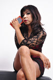 De mooie gekruiste benen van de vrouwenzitting houdt smartphone Stock Afbeeldingen