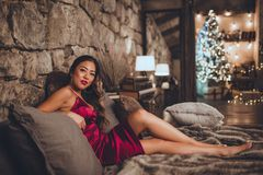 De mooie gelukkige Aziatische vrouw zit in bed thuis dichtbij Kerstmisboom in comfortabel binnenland Binnenland met Kerstmis stock foto