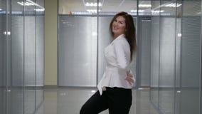 De mooie gelukkige jonge bedrijfsvrouw danste in hallwallbureau stock footage