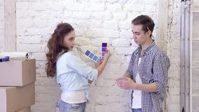 De mooie gelukkige jonge familie die zich tegen een muur bevinden kiest kleur van steekproeven stock videobeelden