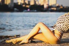 De mooie gelukkige jonge vrouw bevindt zich in een bikini met haar handen omhoog bij de overzeese achtergrond bij de zonsondergan royalty-vrije stock afbeeldingen