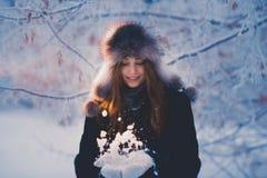 De mooie gelukkige lachende jonge vrouw die de handschoenen dragen die van de de winterhoed met sneeuw worden behandeld schilfert stock fotografie