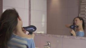 De mooie gelukkige meisjestiener droogt haar met droogkap en zingt en danst voor een spiegel in de langzame badkamers stock videobeelden