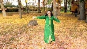 De mooie gelukkige vrouw in een groene kleding, verzamelt bladeren in het de herfstpark en werpt omhoog hen stock footage