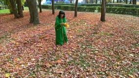 De mooie gelukkige vrouw in een groene kleding, verzamelt bladeren in het de herfstpark en werpt omhoog hen stock video