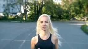 De mooie geschikte en gezonde weg die van de blondevrouw met geschiktheidsdrijver lopen stock footage