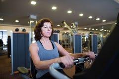 De mooie geschikte hogere vrouw in gymnastiek cardio doen werkt uit stock foto's