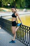 De mooie geschikte vrouwelijke model doende rek die van het geschiktheidsmeisje na training buiten door het meer in de de zomerti royalty-vrije stock fotografie