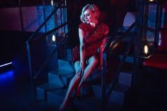 De mooie glam blonde vrouw met provocatief maakt omhoog het dragen van de rode korte gepaste zitting van de lovertjekleding op de stock fotografie
