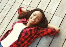 De mooie glimlachende jonge Afrikaanse vrouw ontspande op houten vloer met handen achter hoofd, die een rood geruit overhemd drag Royalty-vrije Stock Foto's