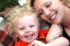 De mooie, glimlachende jonge moeder en wapens die van de zoonsverbinding op deken leggen Royalty-vrije Stock Foto's
