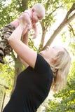 De mooie, glimlachende jonge moeder houdt haar babyjongen in uitgestrekte wapens tegen royalty-vrije stock fotografie