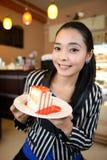 De mooie glimlachende jonge vrouw met een cake stock foto