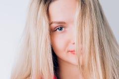 De mooie glimlachende vrouw die met schone huid, natuurlijke make-up de camera op een lichte achtergrond bekijken, sluit omhoog p stock afbeeldingen