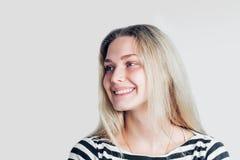 De mooie glimlachende vrouw met schone huid, de natuurlijke make-up en de witte tanden die aan de kant exemplaar bekijken plaatse royalty-vrije stock foto's