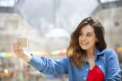 De mooie, glimlachende vrouw neemt een beeld van zich met een smartp Royalty-vrije Stock Afbeeldingen