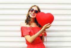 De mooie glimlachende vrouw in rode kleding en de zonnebril met het hart van luchtballons geven het lopen bij stad over wit gesta Stock Fotografie